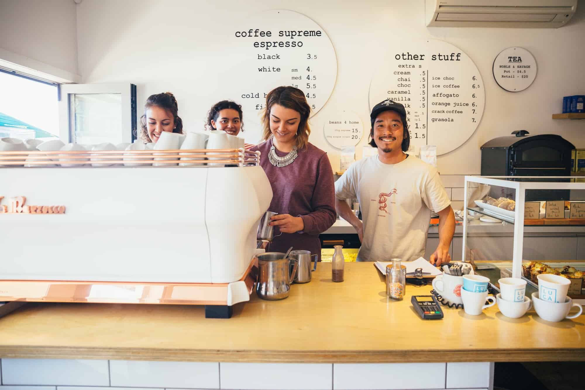young people working and smiling behind coffee shop counter